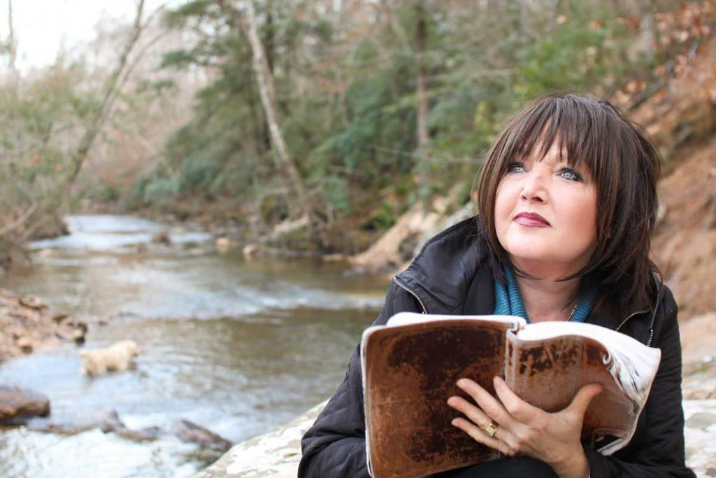 Karen Wheaton reading bible by the creek bed